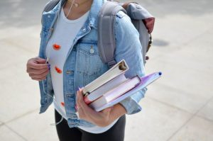 young woman carrying books